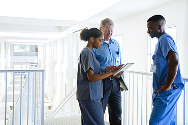 Doctor and nurses using digital tablet near staircase