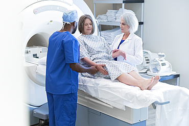 Doctor and nurse helping patient at scanner