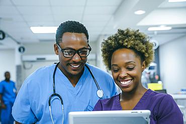 Smiling black nurses using digital tablet