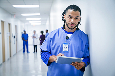 Smiling nurse leaning on wall in hospital using digital tablet