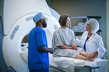 Doctor and technician talking to patient at scanner
