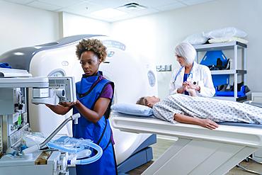 Technician preparing scanner for doctor comforting patient