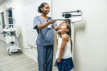 Nurse measuring height of girl