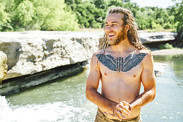 Smiling Caucasian man with chest tattoo standing near river
