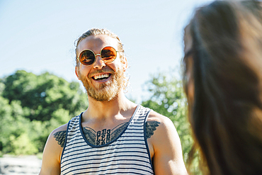 Caucasian man with chest tattoo laughing outdoors