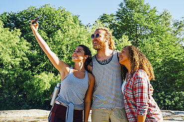 Friends posing for cell phone selfie outdoors
