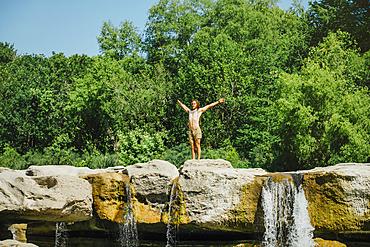 Caucasian man standing on rocks near waterfalls