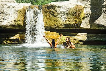 Caucasian couple swimming near waterfall