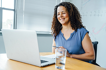 Mixed race businesswoman smiling at laptop