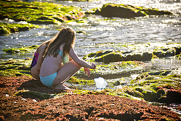 Crouching Caucasian girls exploring tide pools with net