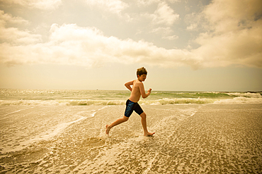 Caucasian boy running in ocean waves