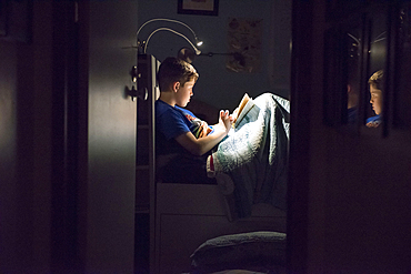 Caucasian boy reading book in bed at night