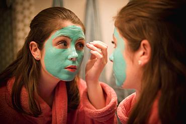 Caucasian girl applying facial mask in mirror