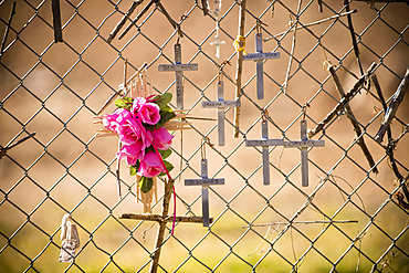 Crucifixes and flowers hanging on memorial fence