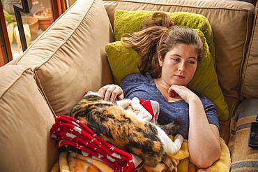 Caucasian girl laying on sofa petting cat