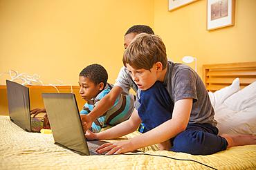 Boys sitting on bed using laptops