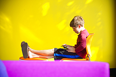 Caucasian boy relaxing and reading digital tablet