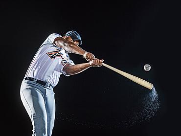 Water splashing from swinging bat of black baseball player
