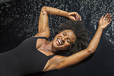 Laughing black woman laying in water
