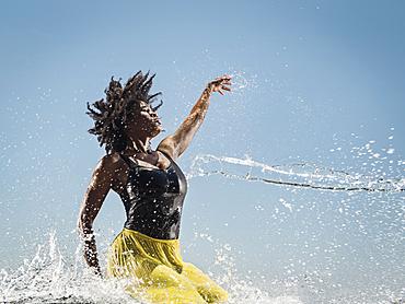 Water spraying on black woman dancing