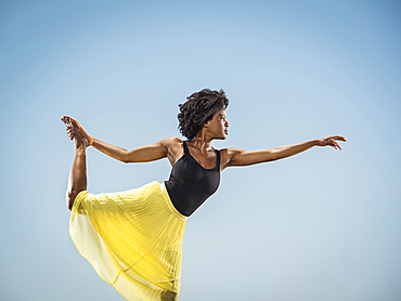 Black woman standing on one leg holding foot