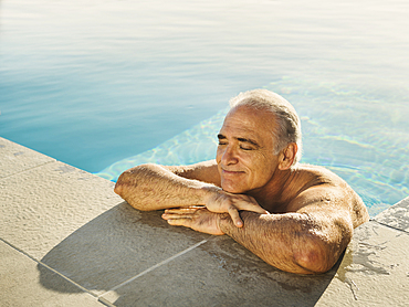Portrait of Caucasian man relaxing in swimming pool