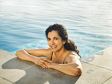 Portrait of Hispanic woman relaxing in swimming pool