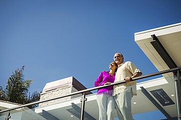 Smiling couple standing on modern balcony