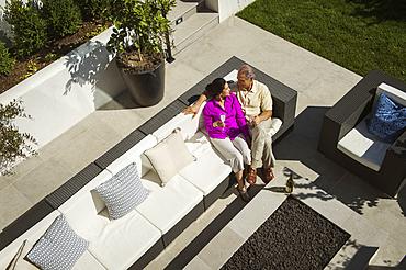 Older couple relaxing on modern backyard patio
