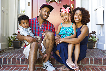 Portrait of smiling mixed race family sitting on front stoop