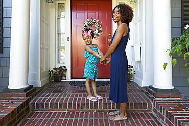 Portrait of smiling mixed race mother and daughter on front stoop