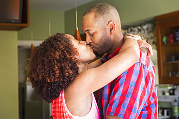 Mixed race couple kissing in kitchen