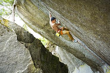 Mixed race boy rock climbing
