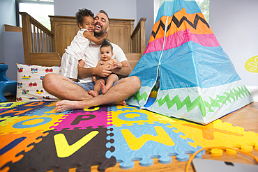 Father sitting on playroom floor holding son and daughter
