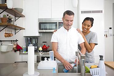 Woman watching man washing baby bottle