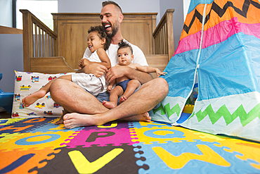 Father sitting on floor of playroom holding son and daughter