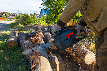 Caucasian man cutting logs with chainsaw