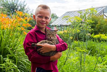 Caucasian boy holding cat on farm