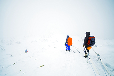 Caucasian hikers carrying skis on mountain