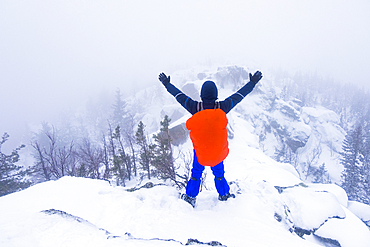 Caucasian hiker waving on snow covered mountain