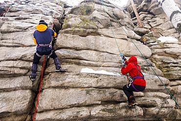 Caucasian man and woman rock climbing