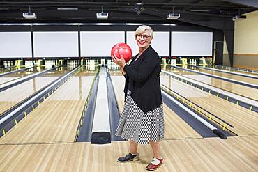 Portrait of Caucasian woman holding bowling ball near lane