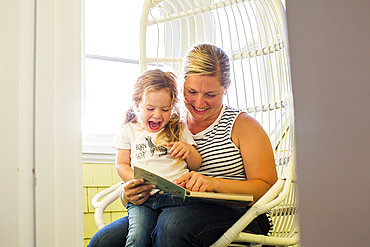 Caucasian mother reading book to excited daughter sitting on lap