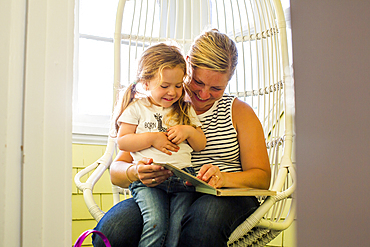 Caucasian mother reading book to daughter on lap
