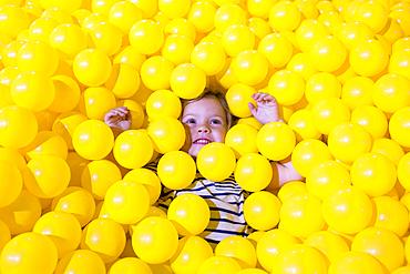 Caucasian girl laying in pile of yellow balls