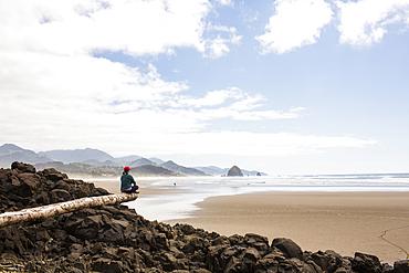 Caucasian woman sitting on log on rocks at beach