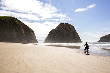 Distant Caucasian woman riding bicycle on beach