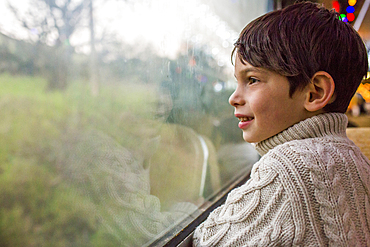 Mixed Race boy looking out train window