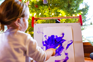 Caucasian girl painting with purple paint on paper