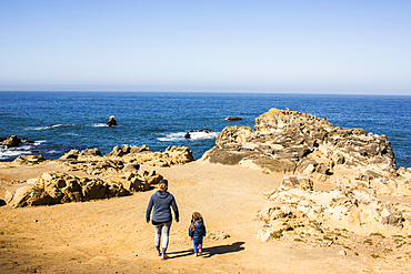 Caucasian mother and daughter walking near ocean